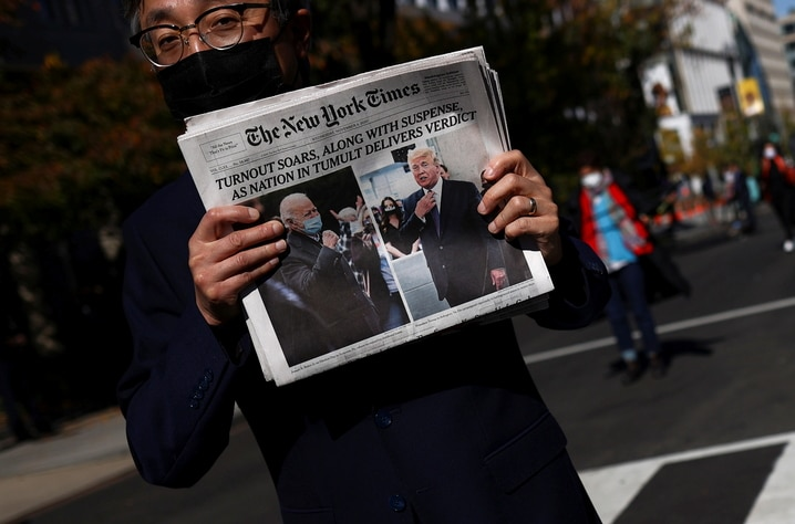 A man holds a newspaper on Black lives Matter plaza near the White House after Election Day in Washington