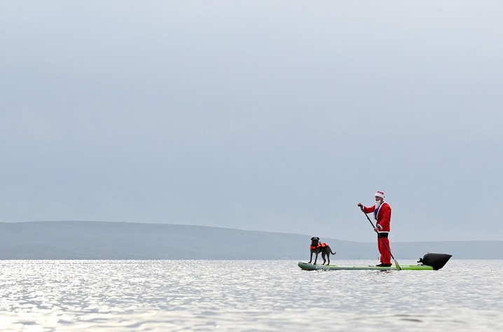 A man dressed as Santa Claus paddles on a board with his dog in Galway Bay