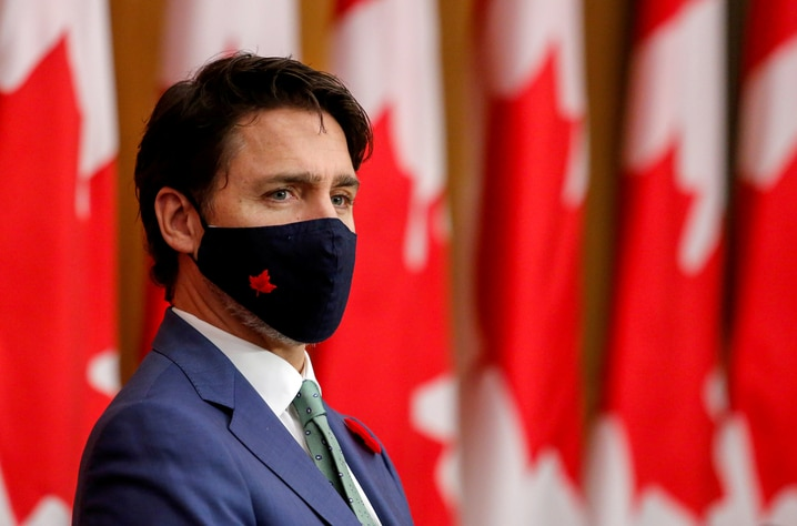 FILE PHOTO: Canadian Prime Minister Justin Trudeau listens while wearing a mask at a news conference in Ottawa