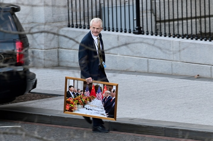 White House advisor Navarro leaves the West Wing of the White House with a photograph of U.S. President Trump and Chinese President Xi in Washington