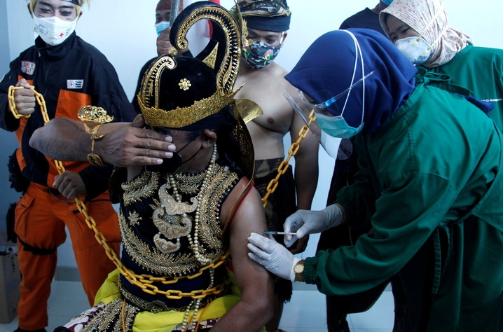 An Indonesian healthcare worker injects a dose of Sinovac's vaccine to a man dressed in Indonesia's traditional human puppet costume, as Indonesia drives mass vaccination for the coronavirus disease (COVID-19), at a hospital in Solo