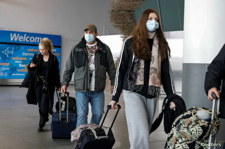 Travelers wear face masks as a preventive measure during the outbreak of coronavirus disease (COVID-19) as they arrive at John…