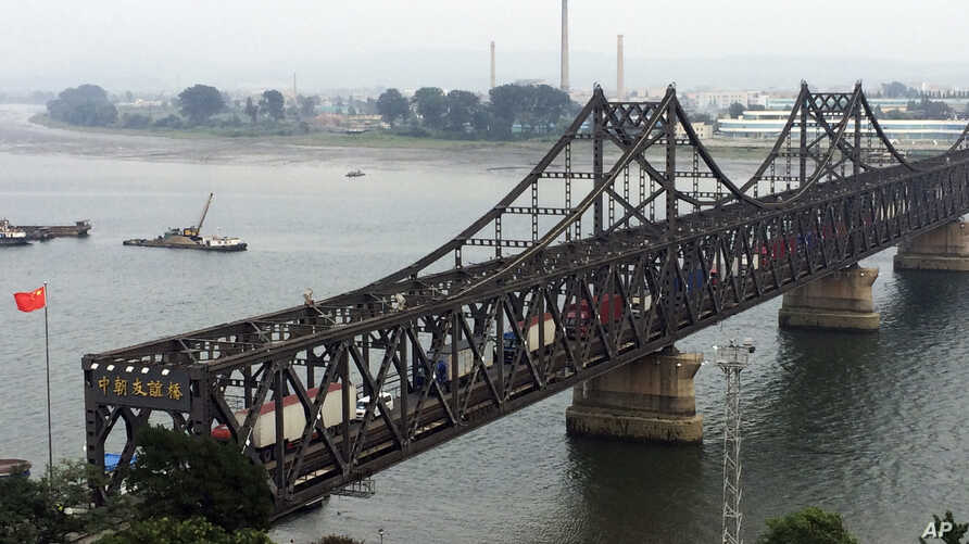 FILE - Trucks cross the friendship bridge connecting China and North Korea in the Chinese border town of Dandong, opposite the North Korean town of Sinuiju, Sept. 4, 2017.