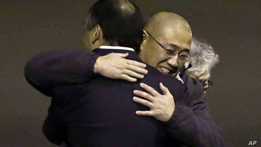 FILE - Kenneth Bae, center, who had been held in North Korea since 2012, is hugged after arriving at Joint Base Lewis-McChord, Washington, Nov. 8, 2014.