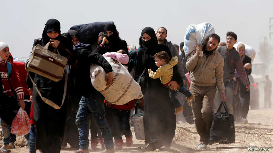 People flee the rebel-held town of Hammouriyeh, in the village of Beit Sawa, eastern Ghouta, Syria, March 15, 2018.