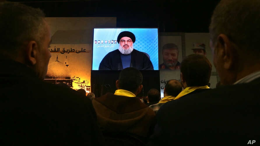Hezbollah leader Sheikh Hassan Nasrallah speaks via video link to supporters during a ceremony marking the death of six Hezbollah fighters and an Iranian general killed in an Israeli airstrike in Syria's Golan Heights last week, in the southern suburb of