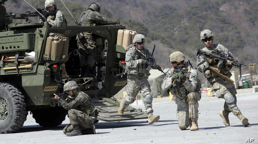 FILE - U.S. Army and South Korean soldiers take their positions during a live-fire exercise at the Rodriquez Multi-Purpose Range Complex in Pocheon, north of Seoul, South Korea, March 25, 2015.