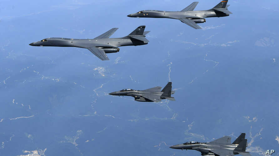 FILE - In this June 20, 2017, file photo provided by South Korean Defense Ministry, U.S. Air Force B-1B bombers, top, and second from top, and South Korean fighter jets F-15K fly over the Korean Peninsula, South Korea. A South Korean lawmaker said Oct....