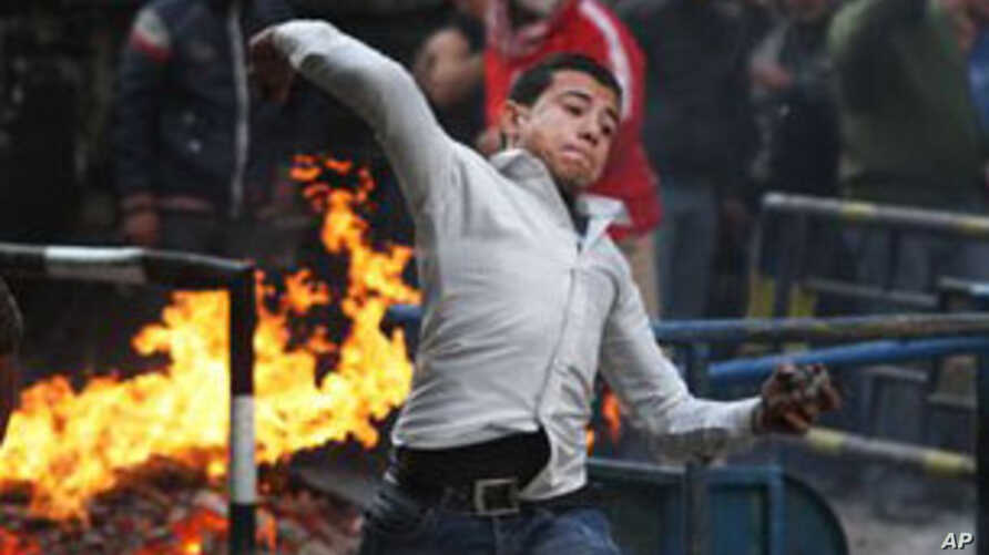 An Egyptian protester throws rocks toward Egyptian riot police in Cairo, Egypt, Monday, Nov. 21, 2011. Security forces fired tear gas and clashed Monday with several thousand protesters in Cairo's Tahrir Square in the third straight day of violence that h