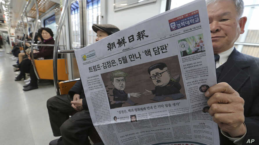 A passenger reads a newspaper with headline of a planned summit meeting between North Korean leader Kim Jong Un and U.S. President Donald Trump, left, at subway train in Seoul, South Korea, March 10, 2018. The White House tried to swat away criticism F...