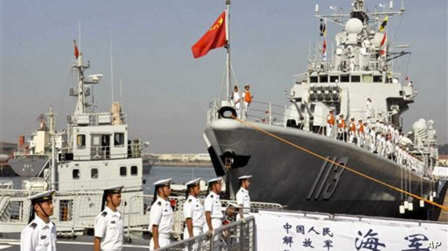 In this Tuesday, Aug. 20, 2013 photo, Chinese navy sailors stand on the guided-missile destroyer, Qingdao, right, before departure for a naval drill at a military port in Qingdao in east China's Shandong province.  Three Chinese ships are sailing east to