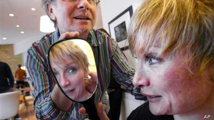 Melissa Rayworth reacts after getting a haircut from Laurent  D., left, as she undergoes a makeover at his salon Prive in New York, April 22, 2005. (AP Photo/Bebeto Matthews)
