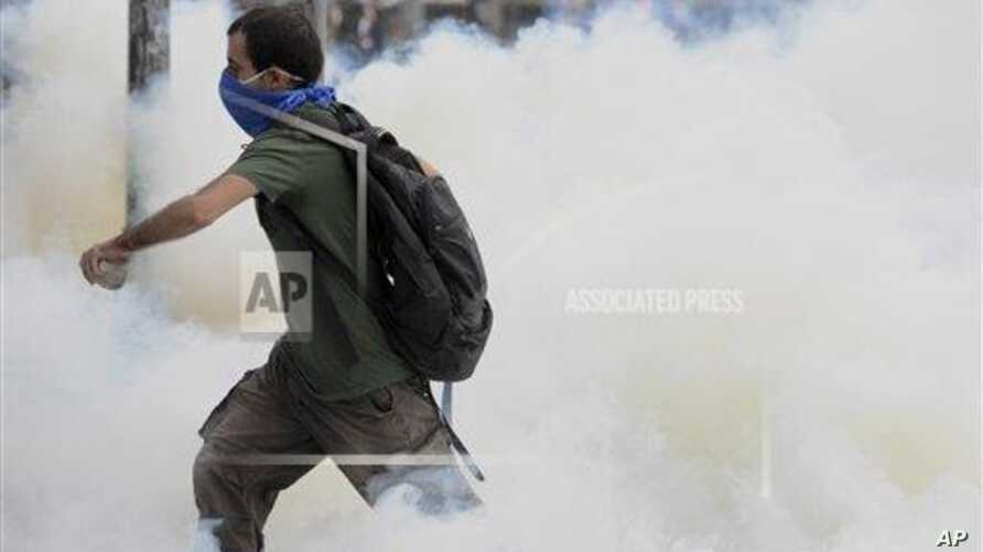 A man runs through smoke of tear gas fired up by riot police in Istanbul, Turkey, Friday, May 31, 2013. Riot police used tear gas and pressurized water to quash a peaceful demonstration by hundreds of people staging a sit-in to try to prevent the demoliti