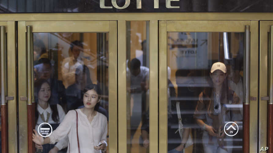 People come out from Lotte Group office in Seoul, South Korea, Friday, Aug. 26, 2016.