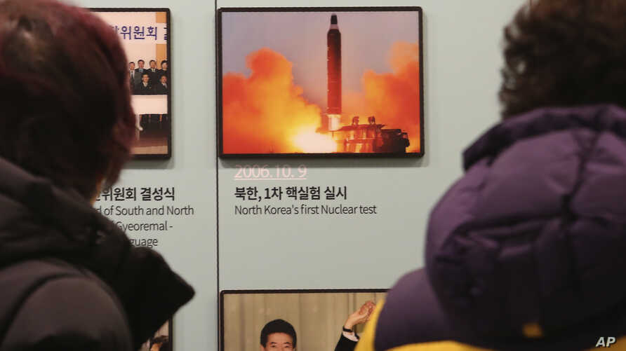 Visitors watch a photo showing North Korea's missile launch at the Unification Observation Post in Paju, South Korea, near the border with North Korea, Dec. 13, 2019.
