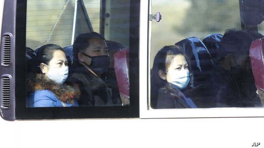 People wear masks as they ride on a public bus in Pyongyang, North Korea, Feb. 26, 2020.