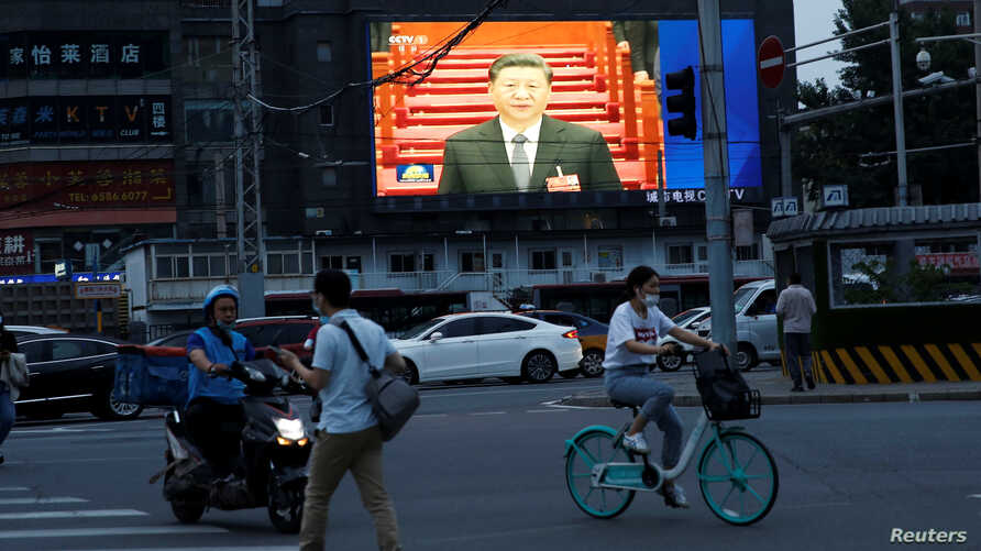 A giant screen displays news footage of Chinese President Xi Jinping attending the opening session of the National People's…