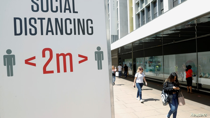 FILE PHOTO: A social distancing sign is seen in Oxford Street, as the outbreak of the coronavirus disease (COVID-19) continues,…