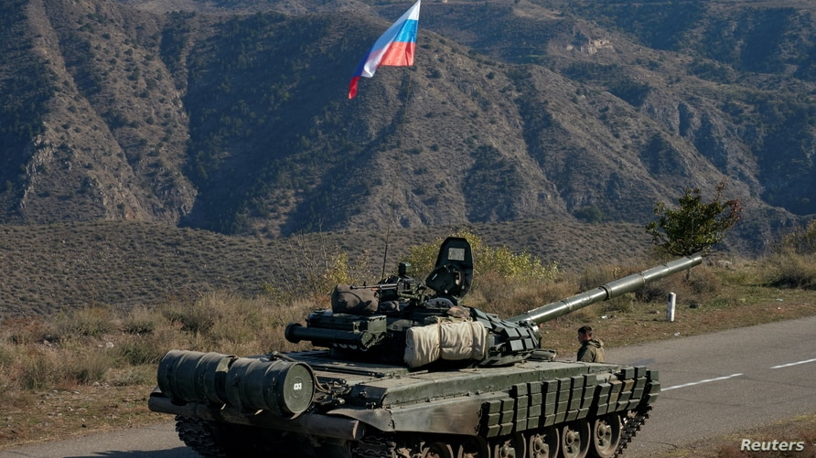 A service member of the Russian peacekeeping troops stands next to a tank near the border with Armenia, following the signing…
