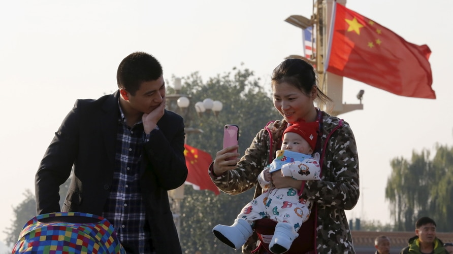 A couple takes pictures with their baby on the Tiananmen Gate in Beijing November 2, 2015. China must continue to enforce its…