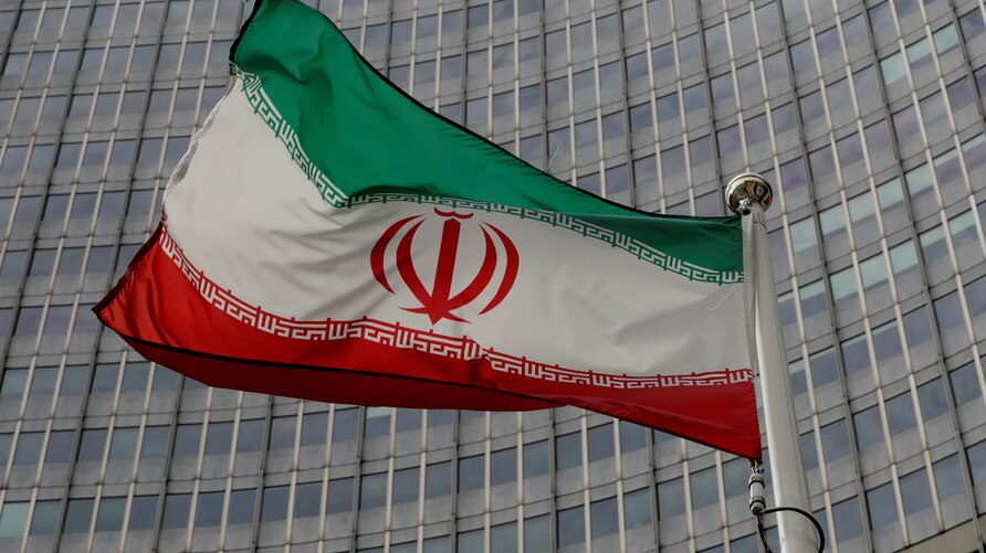 FILE PHOTO: An Iranian flag flutters in front of the International Atomic Energy Agency (IAEA) headquarters in Vienna, Austria,…