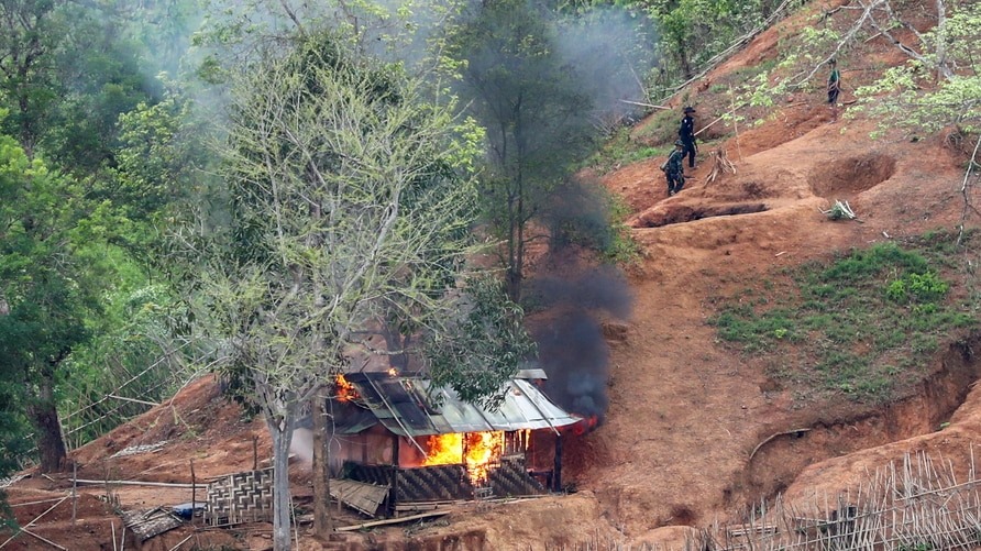 Ethnic minority Karen troops are seen after setting fire to a building inside a Myanmar army outpost near the Thai border,…