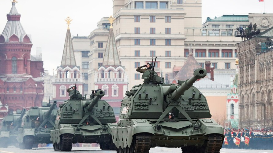 Russian service members drive MSTA-S and Koalitsiya-SV self-propelled howitzers during a military parade on Victory Day, which…