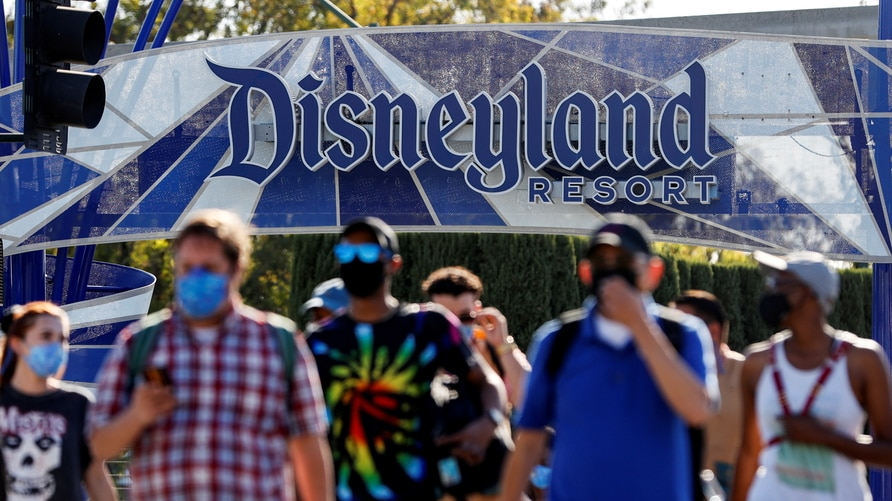 FILE PHOTO: People leave the Disneyland Resort on Disneyland Park and Disney California Adventure's reopening day amidst the…