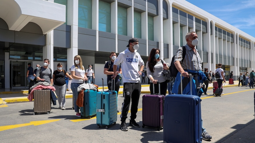 Passengers arriving from Germany and Switzerland line up outside the terminal of the Heraklion airport, as the country's…
