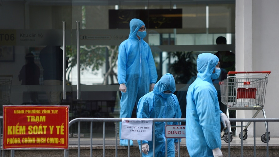 FILE PHOTO: Medical workers in protective suits stand outside a quarantined building amid the coronavirus disease (COVID-19)…