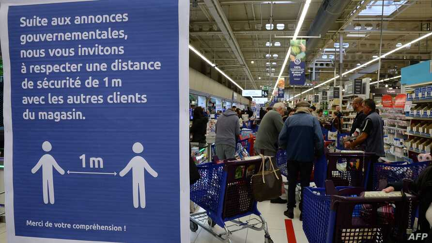 A sign asking shoppers to keep a one metre distance between each other is posted in a supermarket in Merignac, southwestern…