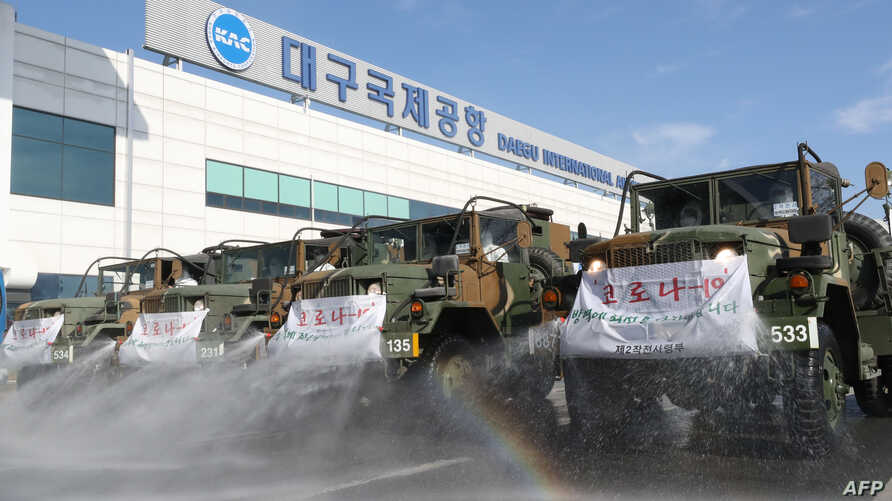 South Korean military vehicles spray disinfectant to help prevent the spread of the COVID-19 coronavirus, at the Daegu…