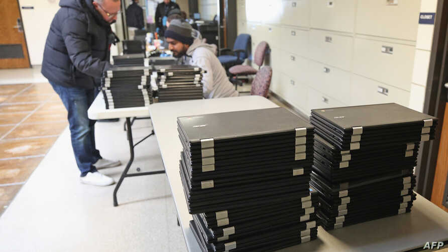 PLAINVIEW, NEW YORK - MARCH 16: Parents of students in the Plainview - Old Bethpage school district pick up Chromebooks at the…
