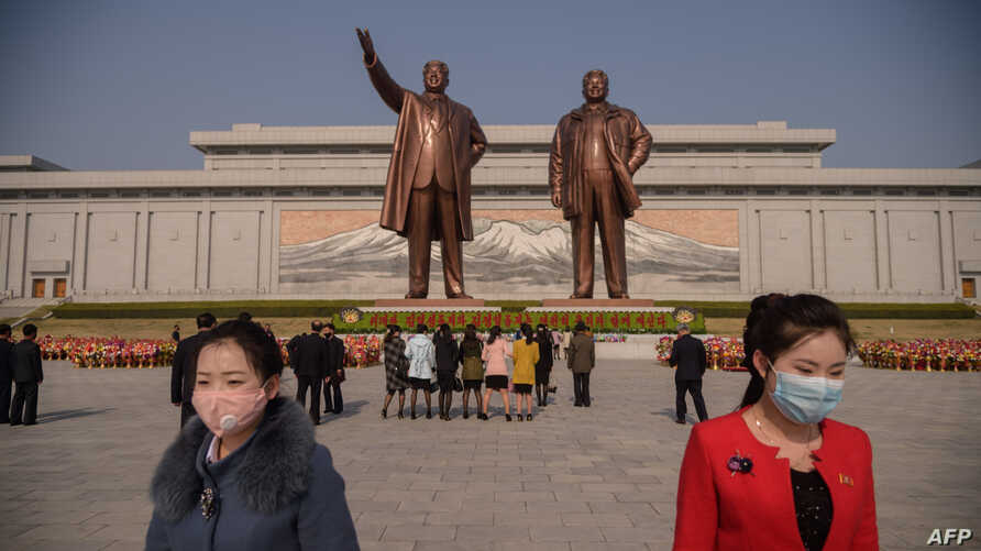TOPSHOT - People wearing face masks leave after laying flowers before the statues of late North Korean leaders Kim Il Sung and…
