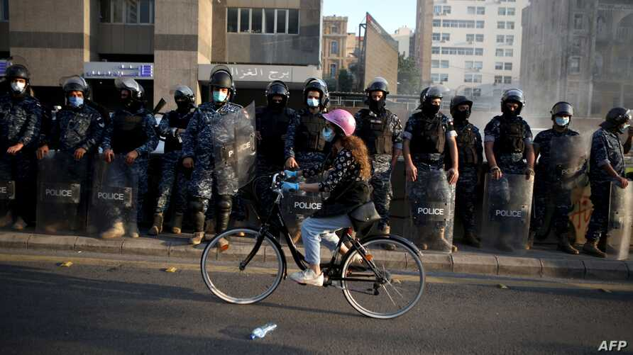 A Lebanese protester rides her bicycle past riot police in the capital Beirut on April 28, 2020, as anger over a spiralling…