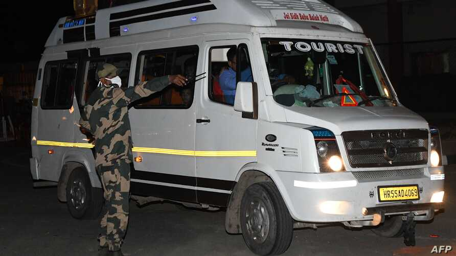 A Border Security Force (BSF) personnel check a mini bus with two officials of the Pakistan High Commission with their families…