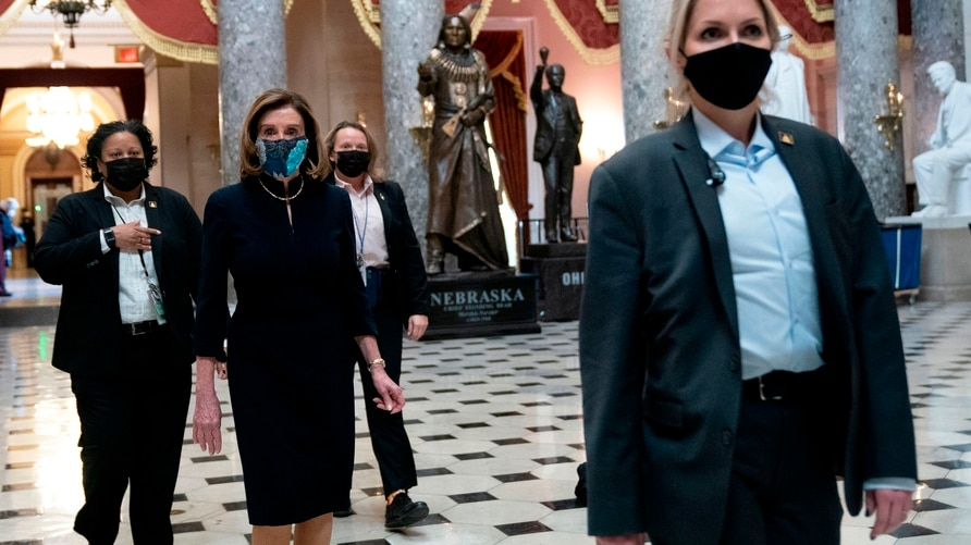 WASHINGTON, DC - JANUARY 13: Speaker of the House Nancy Pelosi (D-CA) (C), surrounded by a security detail, walks to her office…