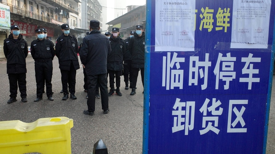 (FILES) This file photo taken on January 12, 2020 shows security guards standing in front of the closed Huanan wholesale…