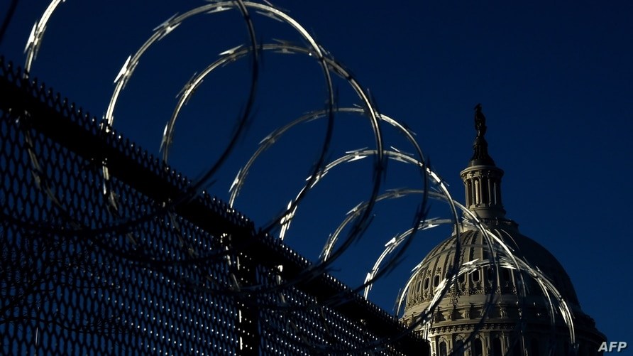 (FILES) In this file photo taken on January 19, 2021, razor wire tops a security fence outside the US Capitol in Washington, DC…
