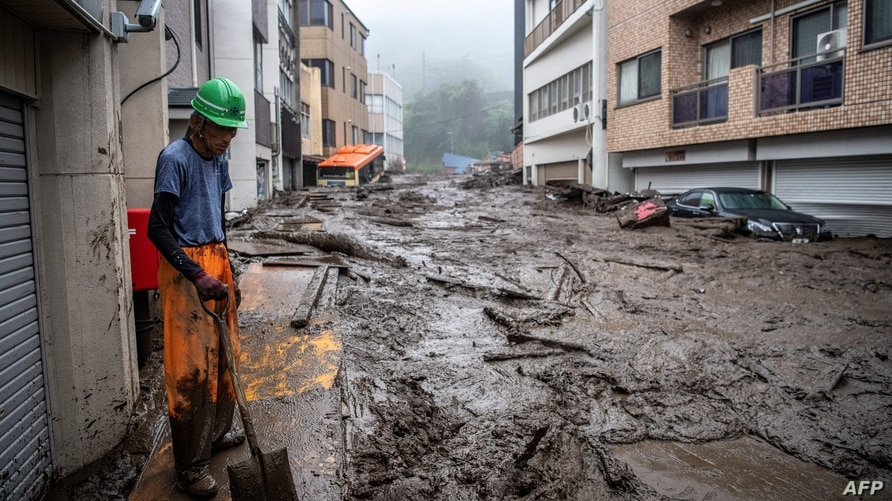 A rescue worker removes mud and debris at the scene of a landslide following days of heavy rain in Atami in Shizuoka Prefecture…