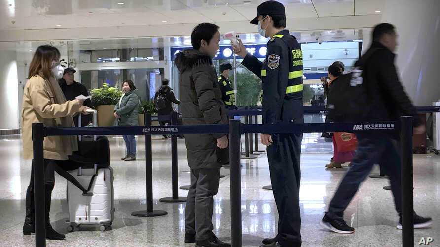 An official uses an infrared thermometer on a traveler at a health screening checkpoint at Wuhan Tianhe International Airport…