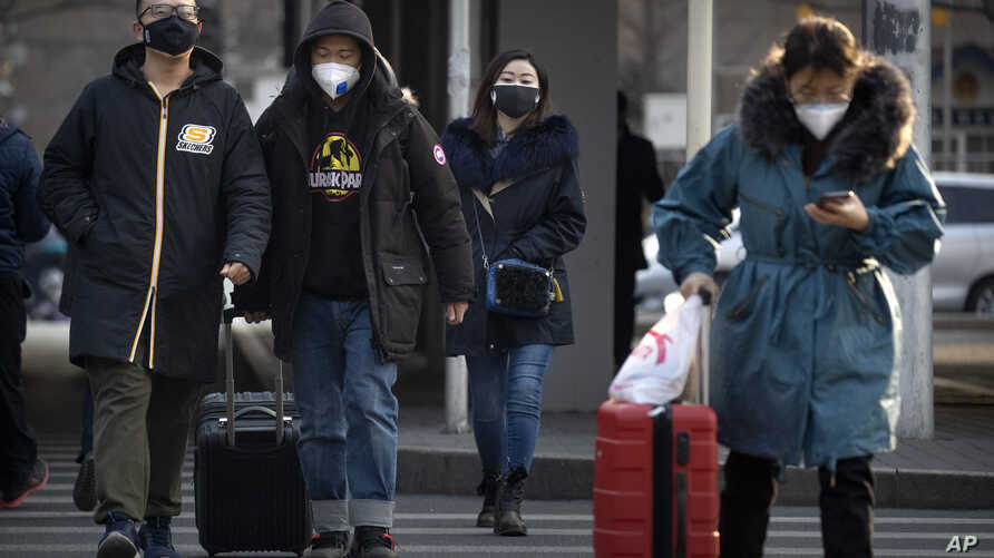 People wear face masks as they walk along a street in Beijing, Wednesday, Jan. 22, 2020. Chinese health authorities urged…