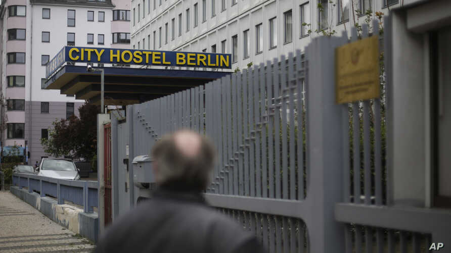 A man stands in front of the entrance of the North Korean embassy and looks to the City Hostel Berlin located in a building of…