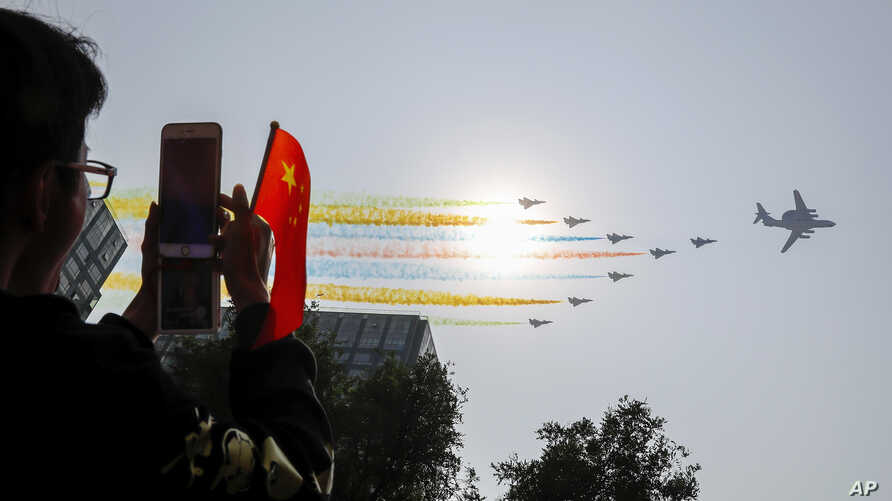 A man uses his smartphone to film Chinese military planes trail colored smoke as they fly in formation past the sun during a…