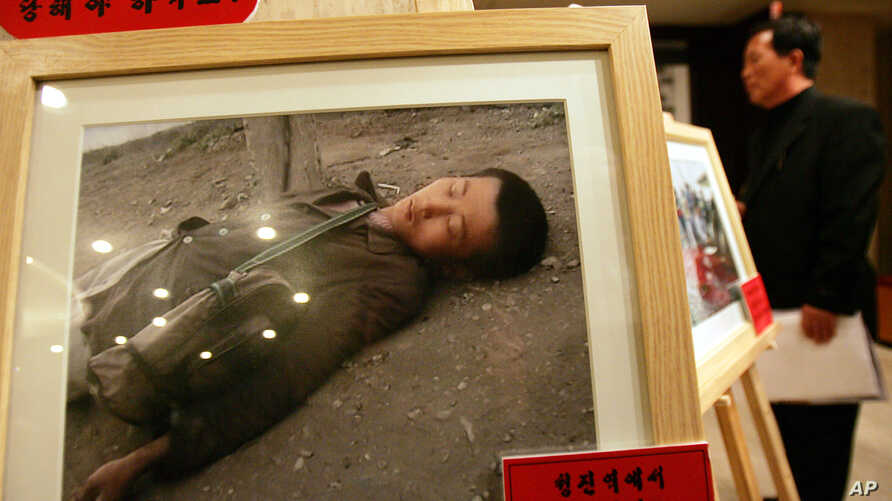 A North Korean defector looks at a pictures showing North Korean children suffering from famine during the Committee for…