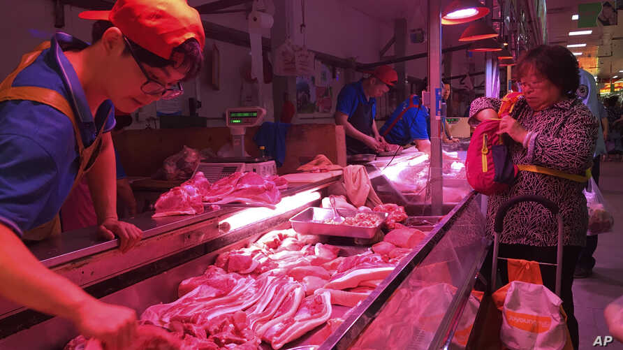 FILE - In this Wednesday, Sept. 11, 2019, file photo, a clerk stacks cuts of pork at a meat market in Beijing. China is…