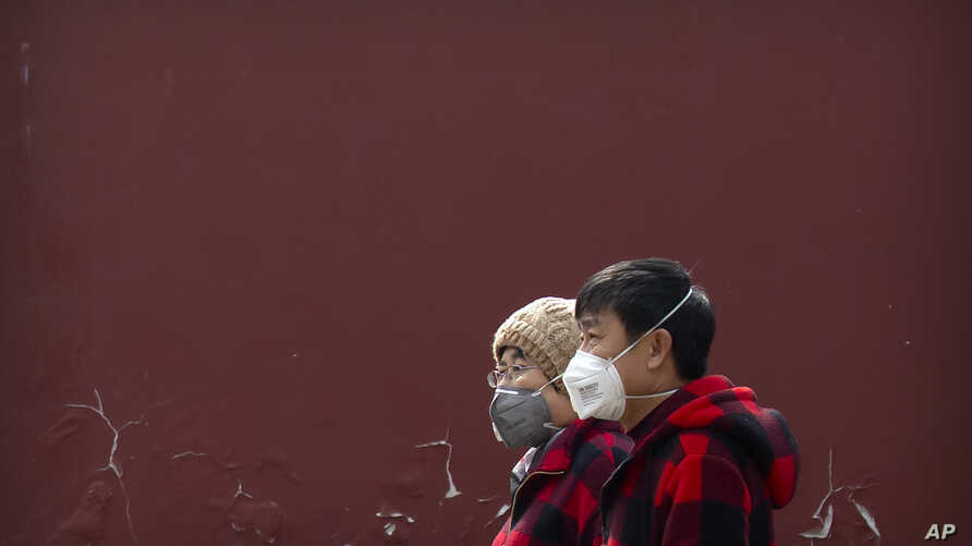 People wearing face masks walk through a public park in Beijing, Friday, Feb. 21, 2020. China reported a further fall in new…