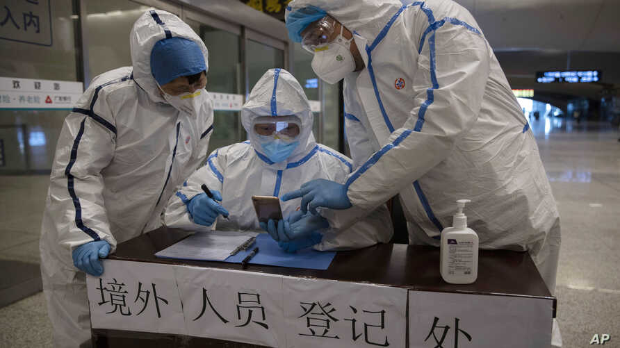 Health workers check details of a passenger arriving from Beijing at the train station in Wuhan in central China's Hubei…