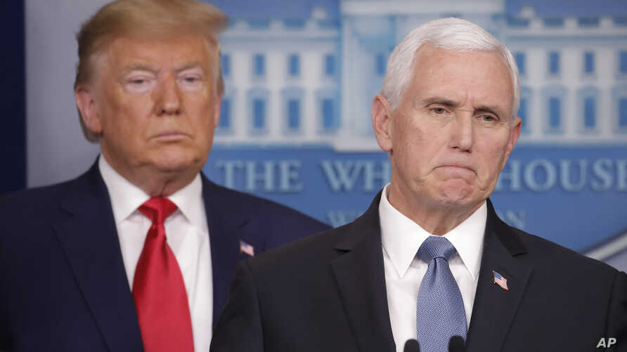 President Donald Trump, left, listens to Vice President Mike Pence, right, as he pauses while speaking to members of the media…