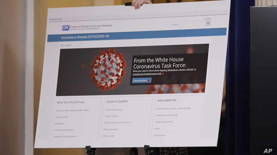 A poster displaying information from the White House Coronavirus Task Force is carried into the briefing room of the White…